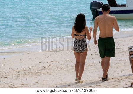 Unidentified Couple With Bikini Wear Walk In The Beach At Mantanani Island, Borneo