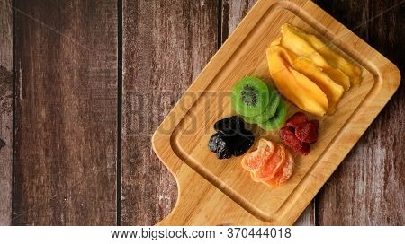 Mixed Dried Food In A Wooden Plate With Wood Table Background. Copy Space, Top View