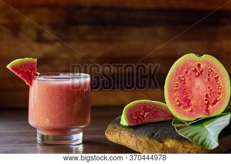 Delicious Red Guava Juice Alongside A Slice Of Guava, In The Background Guavas And Leaves On Rustic