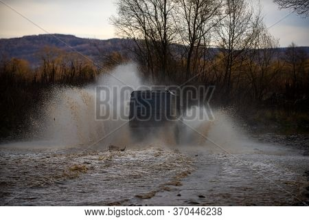 Offroad Car. Offroad Vehicle Coming Out Of A Mud Hole Hazard. Mudding Is Off-roading Through An Area