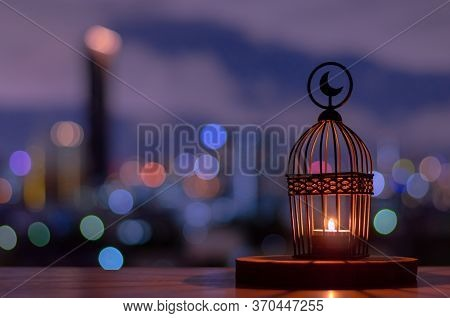 Lantern That Have Moon Symbol On Top Put On Wooden Tray With Dusk Sky And City Bokeh Light Backgroun