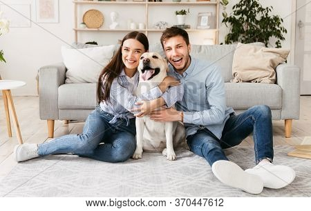 Happy Loving Family Concept. Portrait Of Beautiful Couple With Dog Sitting On The Floor In Modern Ap