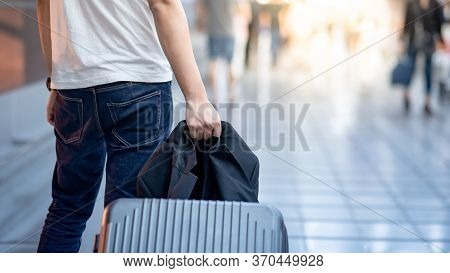 Vacation Trip Or Travel Abroad Concept. Immigration And Baggage Claim. Tourist Man Walking With Suit