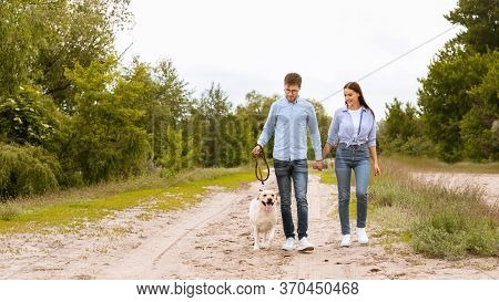 Casual Lifestyle Concept. Lovely Couple Taking Their Obedient Labrador For A Walk Outdoors, Copy Spa