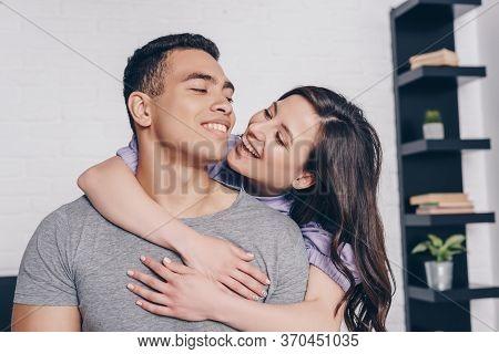 Woman Embracing Handsome Bi-racial Man In Bedroom