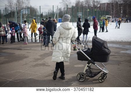Girl With A Baby In A Stroller. Mom Walks In The Park With A Child. A Girl Stands Away From The Crow
