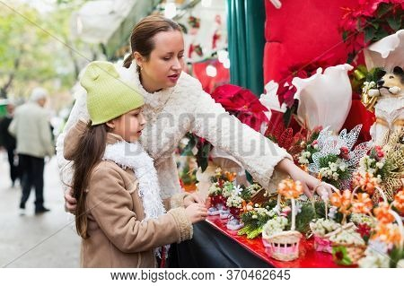 Young Woman With Little Daughter Looking At Adornment With Conifer In Christmas Market. Focus On Gir
