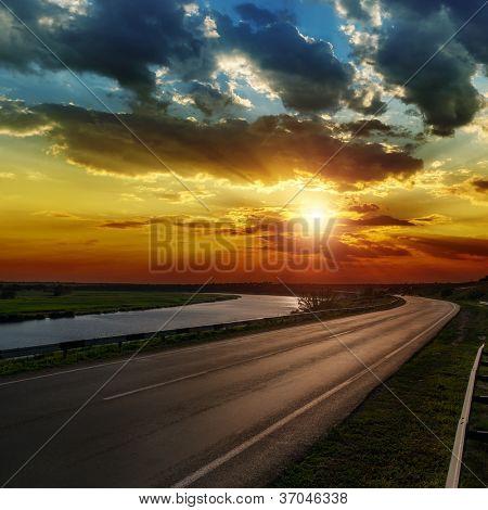 dramatic sunset over asphald road