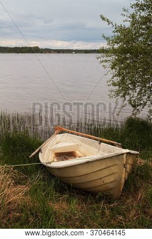 An Old Rowing Boat Lies On The Shore By A Lake At The Rural Finland. The Sun Is Beginning To Set In