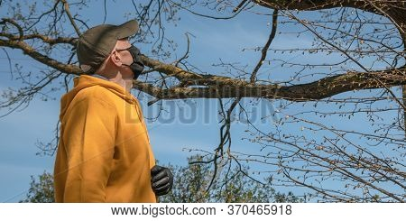 Pensioner In Black Sterile Gloves And Disposable Face Mask Wanders In Village Garden And Looks At La