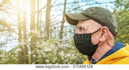 Senior Man In Cap And Black Face Mask Stands In Garden Against Blooming Trees At Back Sunlight Close