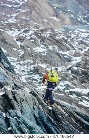 Back View Of Male Mountaineer With Backpack Using Fixed Rope To Climb High Rocky Mountain. Climber A