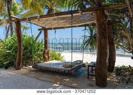 Wooden Swing With A Mattress And Pillows Under A Canopy On The Tropical Beach Near Sea, Island Zanzi