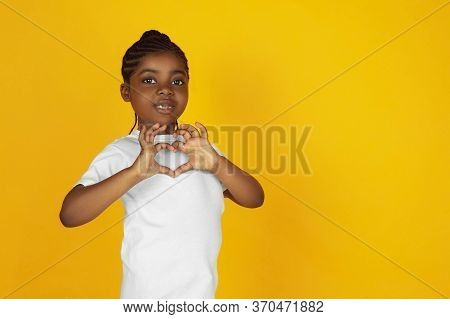 Inspired Showing Heart Sign. Little African-american Girls Portrait On Yellow Studio Background. Che