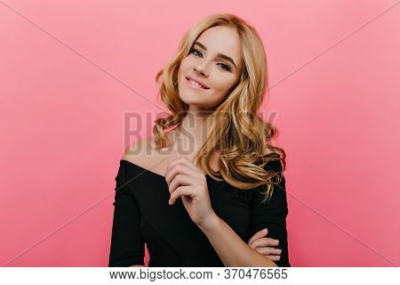 Engaging Blonde Girl In Black Dress Posing With Pleasure On Pink Background. Indoor Photo Of Joyful