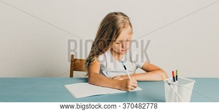 Blonde Girl Sits At A Table And Writes In A Notebook