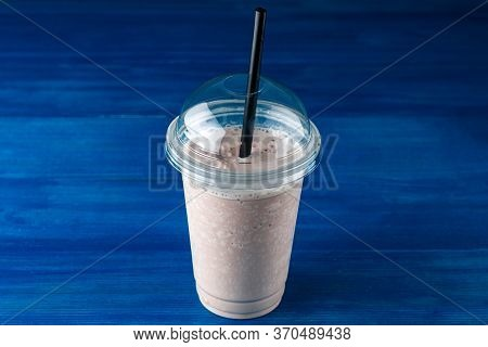 Delicious Chilled Takeaway Chocolate Milkshake In Plastic Glass On A Dark Background. Chocolate Milk