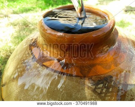 Filling Water In A Clay Pot In Summer During Lack Of Water In Rural Areas And Water Is Overflowing