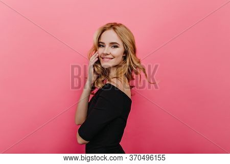 Happy Blonde Girl Posing With Shy Smile. Portrait Of Carefree Fair-haired Woman In Black Outfit Stan