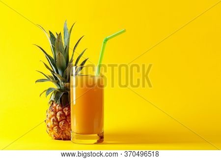 Fresh Pineapple  Juice On A Yellow Background. Copy Space.