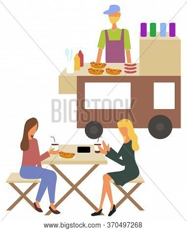 Women Sitting At Table And Eating Hotdog And Drinking Coffee, Seller Male Standing Near Cart With Me