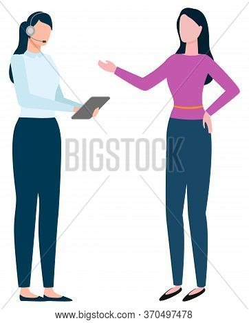 Two Women Standing Together And Talking. Lady In Formalwear With Earphones And Tablet In Hands. Pers
