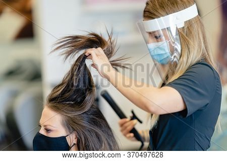 Hairdresser, Protected By A Mask, Combing Her Clients Hair With A Hair Iron In A Salon.