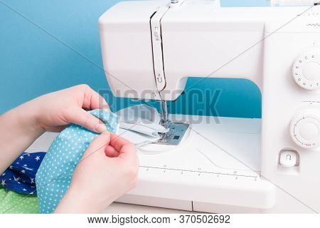 Woman Sews With A Needle A Protective Face Mask Made Of Cotton Fabric, Hand Sewing Concept, Sewing M