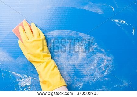 a female hand in a yellow rubber glove washes a blue surface from dirt with a paralon sponge, a trac