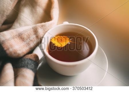 Warm Autumn Cozy Photo: Cup With Tea Or Coffee, A Plaid And An Autumn Yellow Leaf, Autumn Concept