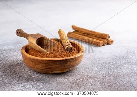 Ceylon Cinnamon Sticks With Cinnamon Powder In Wooden Bowl On Concrete Background. Copy Space.
