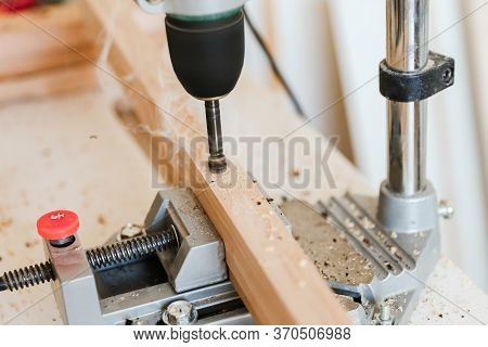 Woodworking With A Vertical Drill To Drill A Hole In A Wooden Block With Wood Shavings And Smoke In