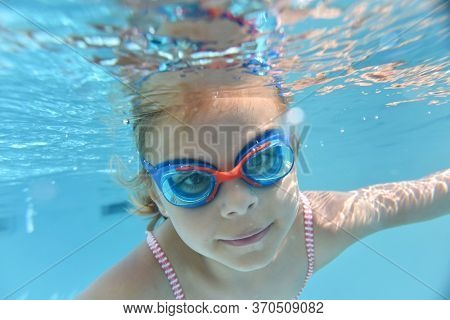 Portrait of cute girl with goggles swimming under pool water