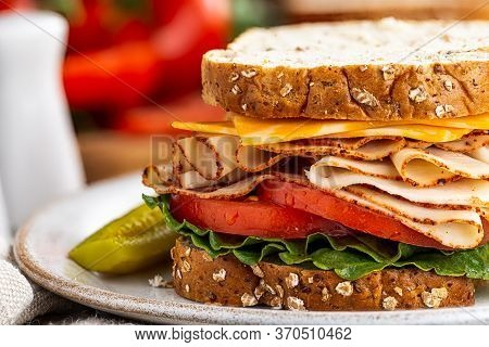Closeup Of Turkey Sandwich With Cheese, Tomato And Lettuce On Whole Grain Bread  With Ingredients In
