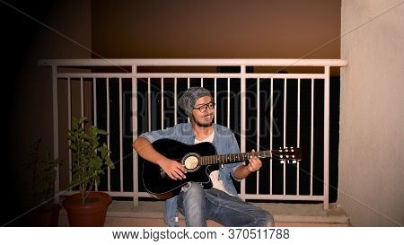 Abstract Background Of Cheerful Smiling Young Man Playing Guitar Sitting Outdoor In Balcony Terrace