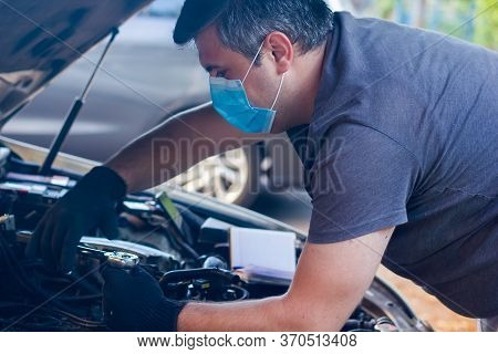 Car Mechanic On Protective Mask Fixing Car Engine, Auto Mechanic Is Repairing Car Engine
