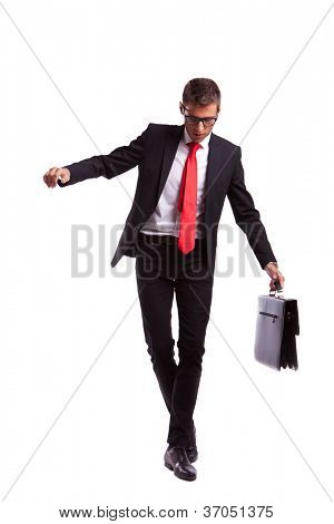 Business man holding a briefcase balancing and walking forward on an imaginary rope
