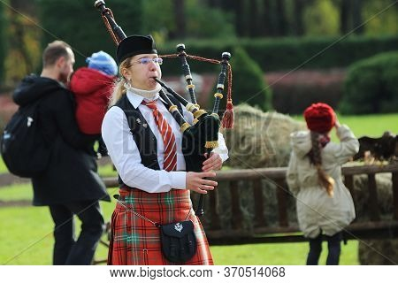 Minsk/ Belarus - October 31 2018: Girl In A National Scottish Costume Plays The Bagpipes In The Park