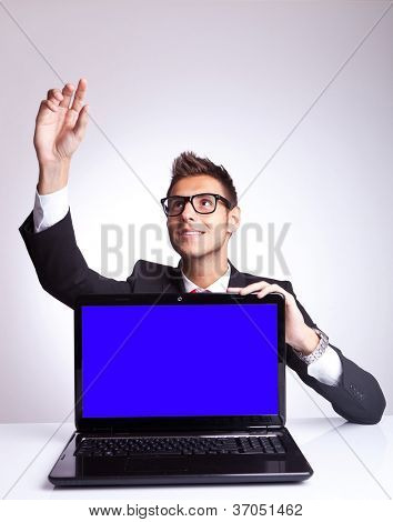 surprised business man at his desk in front of laptop computer, reaching and picking something from above the computer