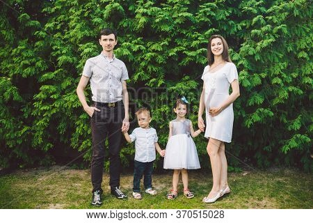 A Diverse Family Photo. Young Pregnant Mother With Her Family In A Park. Pregnancy And Healthy Lifes