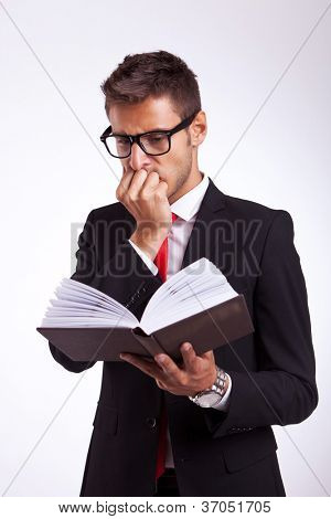 portrait of young shocked business man reading the thriller book