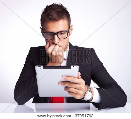 business man looking worried whie reading something on his electronic pad