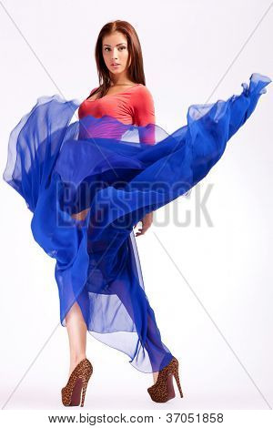 sensual young woman in a blue fluttering dress looking at the camera