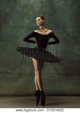 Balanced. Graceful Classic Ballerina Dancing, Posing Isolated On Dark Studio Background. Elegance Bl