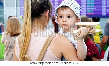 Portrait Of Sad Little Boy Hugging Mother In Airport And Holding Toy Airplane