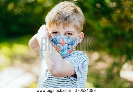 Blond Kid Boy Children Putting On Protective Mask Correctly Covering Face Nose Mouth, Concept Of Pro