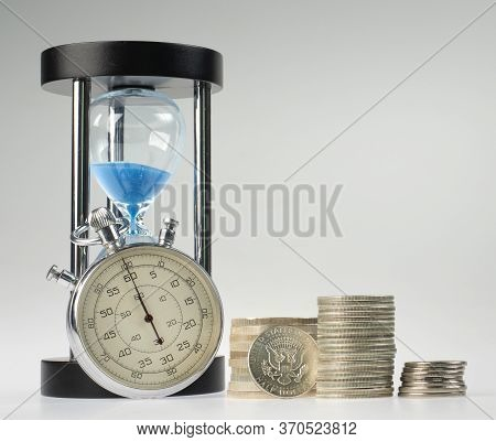 Time And Money. Hourglass And Stopwatch With Stacks Of Silver Coins