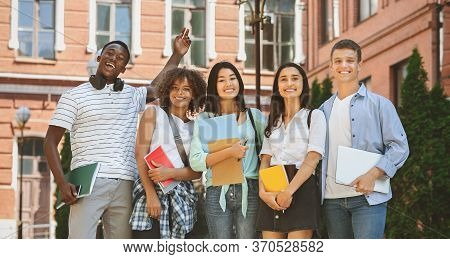 Freshmen Orientation Concept. Group Of First Year Students With Workbooks Posing Together Outdoors,