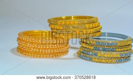 Blue, Golden & Yellow Glass & Metal Bangles On White Background.