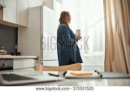 Taking A Break. Young Woman In Casual Clothes Drinking Coffee Or Tea, Looking In The Window While Wo